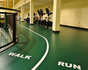 Elevated mezzanine track for indoor running on the field sports