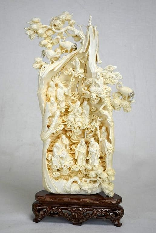 "An extremely intricate ivory carving of twelve men, three cranes, and smoke and foliage. Attached to wood stand inlaid with gold metal. Height - 13 3/8"" 19th Century"