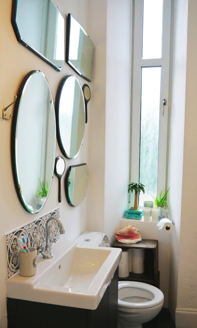 Bathroom with multiple round mirrors hanging. Can't find the perfect mirror for your vanity? We love that this modern, minimalist vanity was paired with simple mirrors of various sizes, arranged haphazardly but still stylishly on the wall. You can also achieve a similar look by pairing mirrors with different frames, some modern, some more ornate.