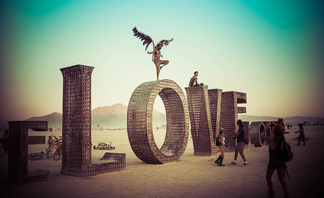 The Love sculpture with one of my Iranian friends dancing in wings on top. #burningman #love #wings #desert #art #photography