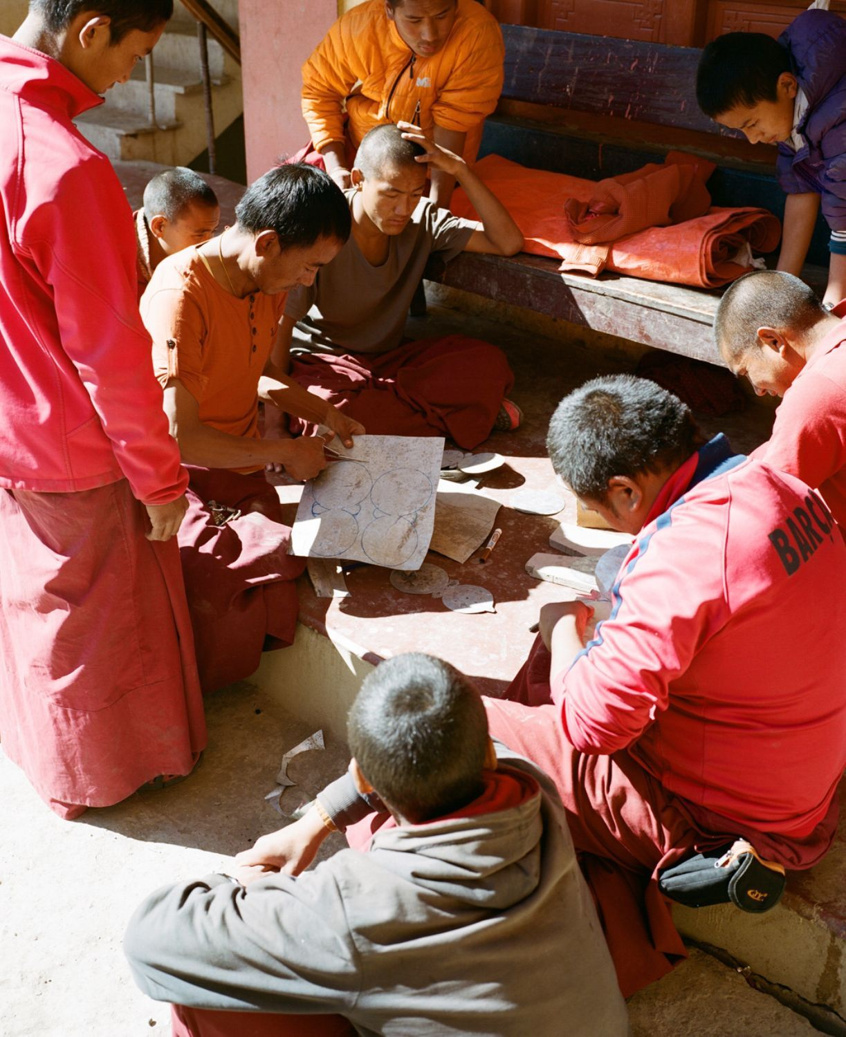 Monks cutting out lotus flowers from sheets of tin. Kagbeni, Upper Mustang.