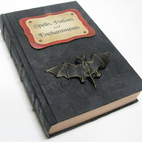 """Grab an old hardcover book, and cover it with black construction paper. Use card stock or construction paper to craft a spooky label highlighting the book's magical contents. For a finishing touch, find a small bat or spider """"talisman"""" at the dime store, and glue it to the cover. Source: Etsy seller ElvesInTheAttic"""