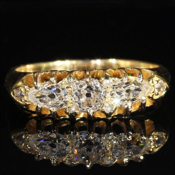 This 18k gold ring holds a total of nine diamonds. The center an old European cut round diamond .4 cts, side diamond pear shaped old cut diamond, weighs .3ct each.