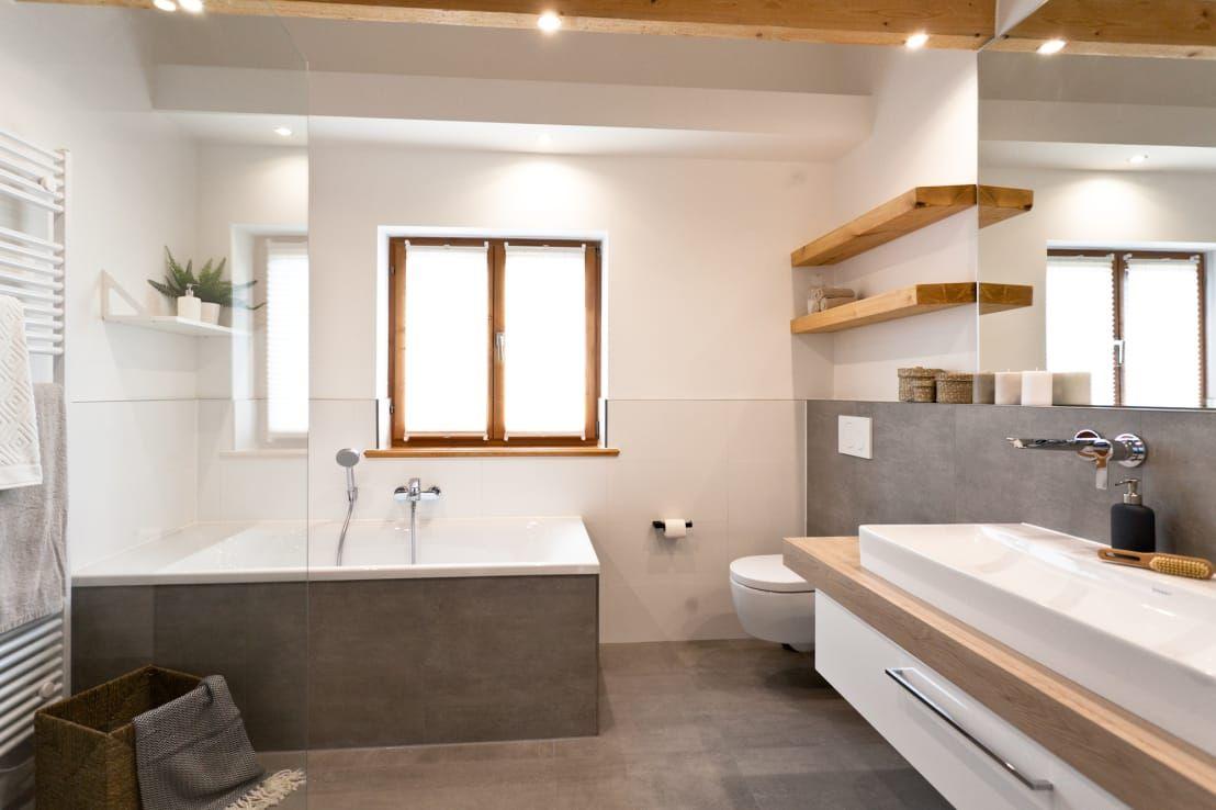 Badsanierung Schickes Wohlfühlbad mit viel Holz und modernen Fliesen in Betonoptik