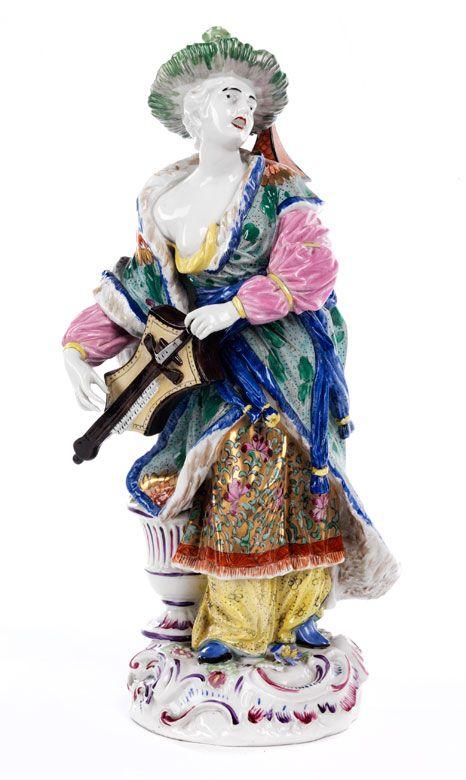 Die Chinesin trägt auf dem Kopf einen Basthut, auf dem Rücken ein Kästchen in Form eines Vogelbauers. Die Figur steht neben einer kannelierten Vase, auf ...