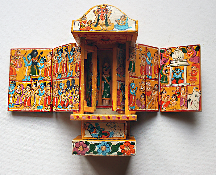 "This exclusive Yellow mustard ""Kawad"" is an amazing folded wooden Hindu temple whose origin is more than 500 years old. Each hinged panel and door show colorful pictures and motifs to illustrate the popular story of Lord Krishna's love of the cow herd girl named Radha.    Hand crafted by artisans of Rajasthan from mango wood, they are a collectors item.  www.theindianweave.com"