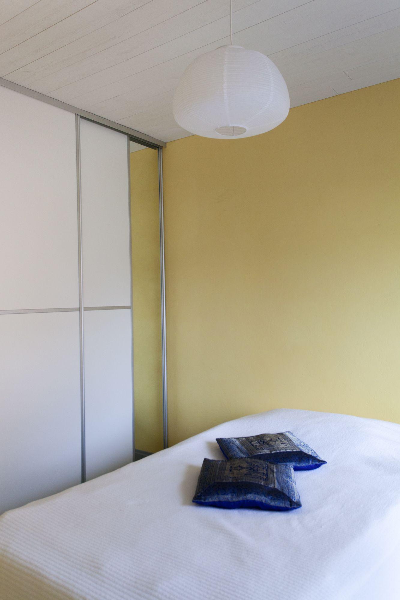 Keltaiset seinät makuuhuoneessa yhdistettynä valkoharmaisiin kaapinoviin luovat positiivista ja harmonista tunnelmaa. Seinät on maalattu Tikkurilan Tunne väri -kokoelman sävyllä J302 Banaani.