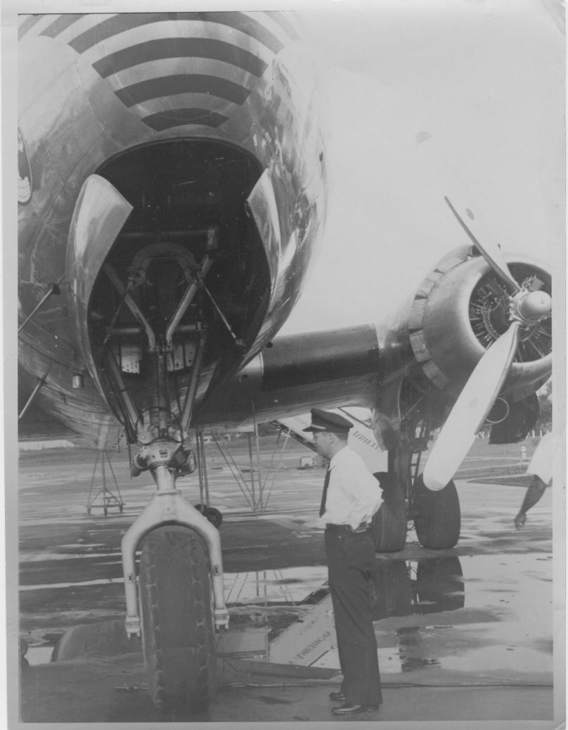 1948 A Pan Am  pilot by the nose wheel of a DC4 aircraft.