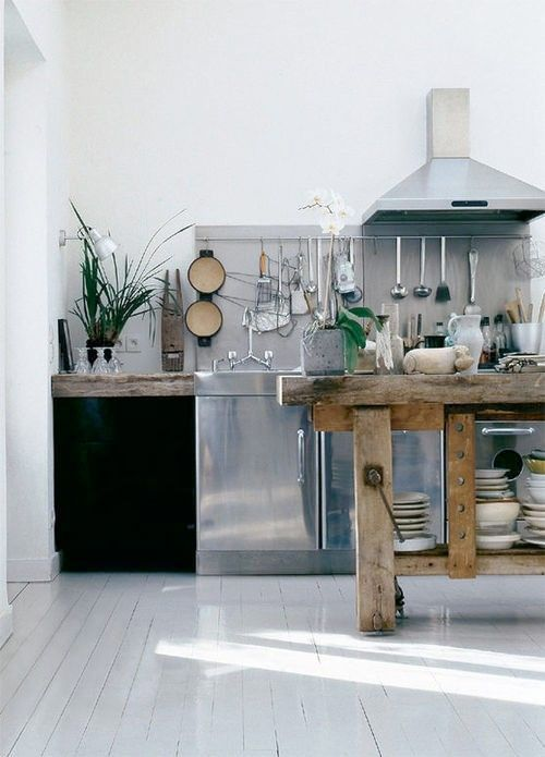 White and stainless steel kitchen with wooden storage.