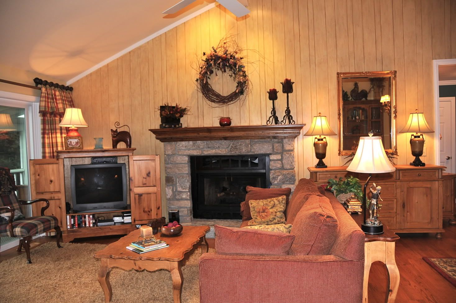 Vaulted ceiling, panelled wall with large stone fireplace