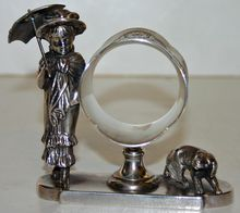Very Rare Figural Napkin Ring - Lady With Parasol and Dog by Tufts. Seldom seen but often wished for, this special silver plate napkin ring from the late 1900's would be a conversation piece at any table. Collect a different one for each place setting.