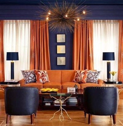 Orange Curtains And Upholstery Against Dark Grey Walls Is An Excellent Pairing That Reads Both Masculi Living Room Orange Living Room Decor Orange Orange Rooms