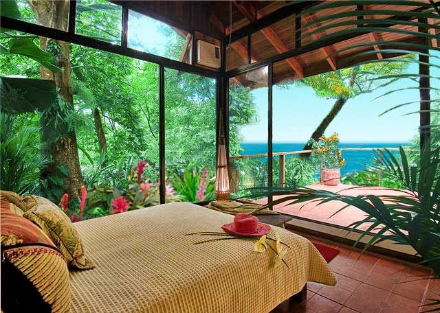 The master bedroom of this vacation home features a wall of windows overlooking rain forest and the pacific coastline