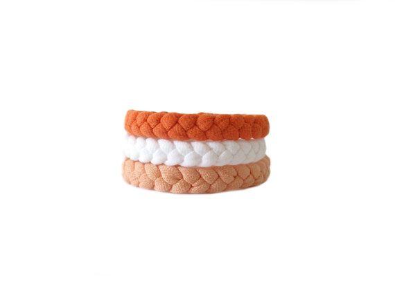 Handmade braided bracelets made from orange, white and peach cotton tshirt yarn.