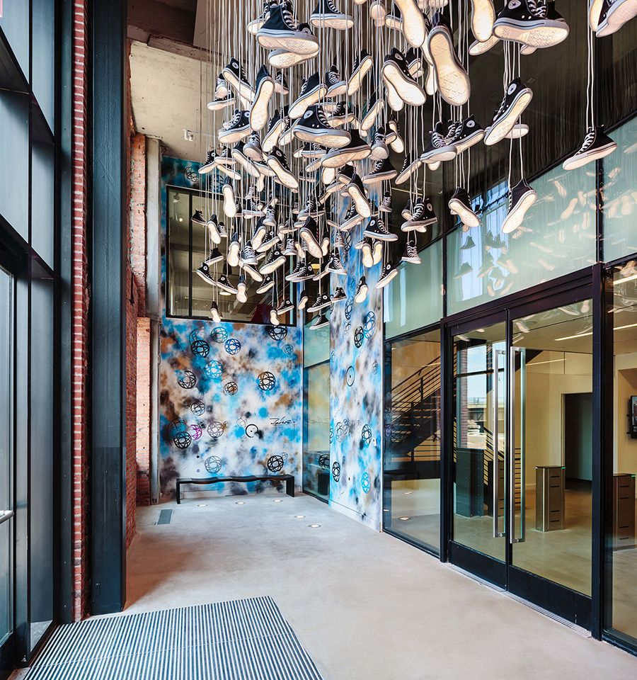 A chandelier of converse sneakers hangs in the entryway of the a chandelier of converse sneakers hangs in the entryway of the companys corporate headquarters on bostons arubaitofo Choice Image