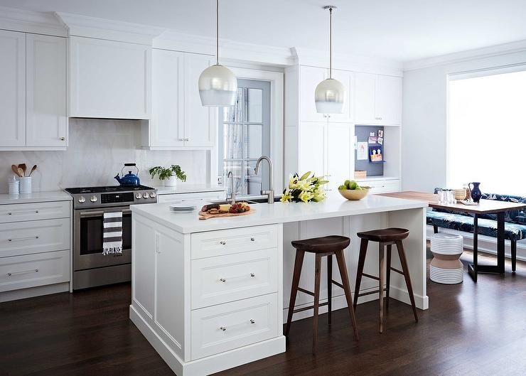 Well appointed white kitchen boasts white and silver pendant lights hung over a white island finished with nickel and glass pulls and a white quartz countertop seating backless wood barstools.