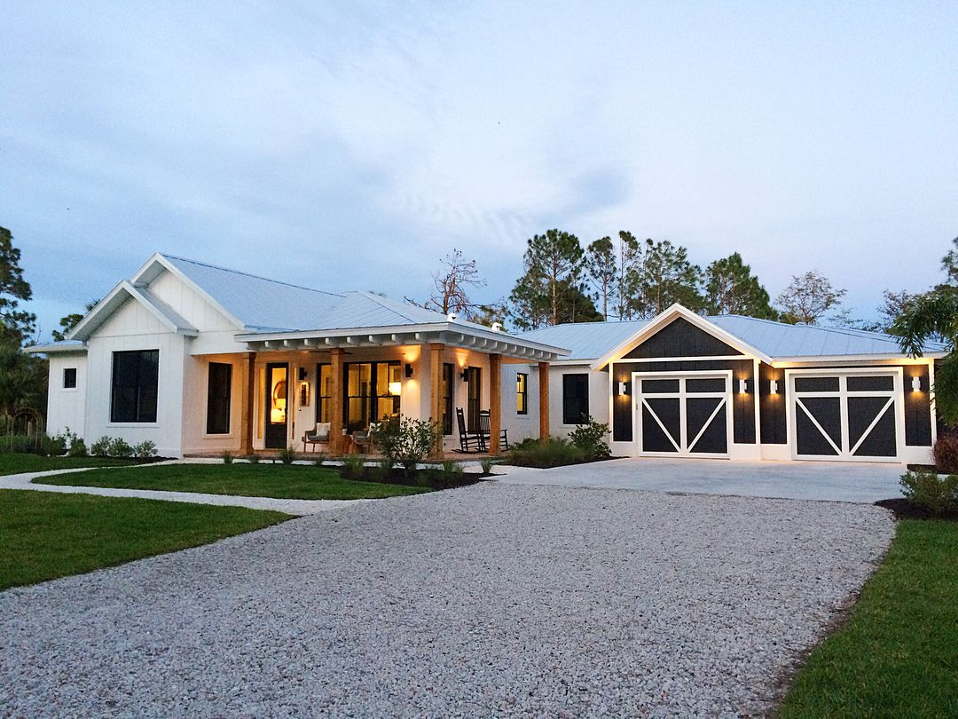 One Story Modern Farmhouse In Naples Florida White Exterior With Navy Blue Black Garage Modern Farmhouse Exterior House Exterior Blue Ranch House Exterior