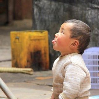 A beautiful little child outside a monastery in Tibet