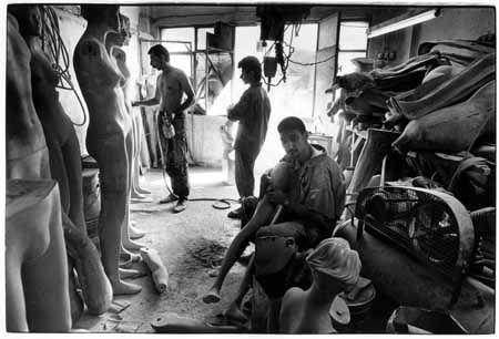 Iranese llegalen aan het werk in een produktieatelier voor etalagepoppen.  Illegal refugees from Iran working in a factory.