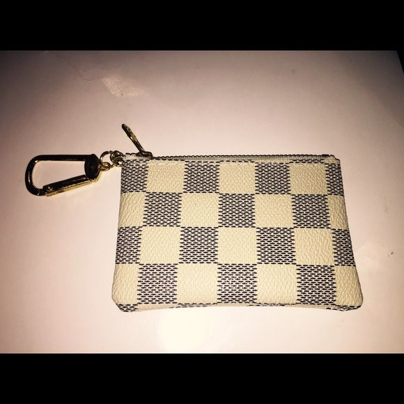 Small White Damier Style Fashion Coin Purse  - new, synthetic (not real) leather, zipper sticks sometimes (you can use lip balm to make it glide easier).   This is a fashion item not associated with any brand.   With that being said I will not  answer questions that have been answered in the description and/or pictures.   If you would like to make an offer please use the make offer link.   Bundles will receive an automatic discount when you use the add to bundle link. Bags