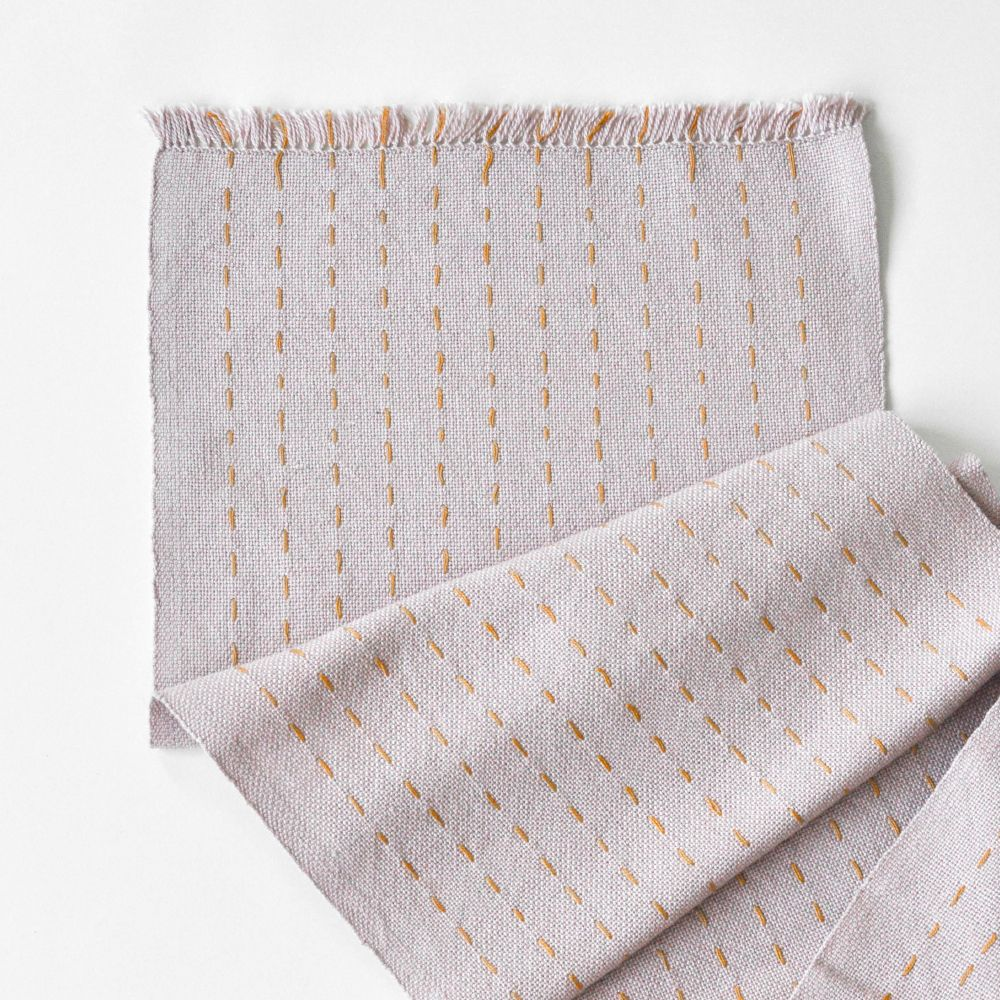 A geometric-patterned table runner woven with gold cotton on a natural cotton warp.
