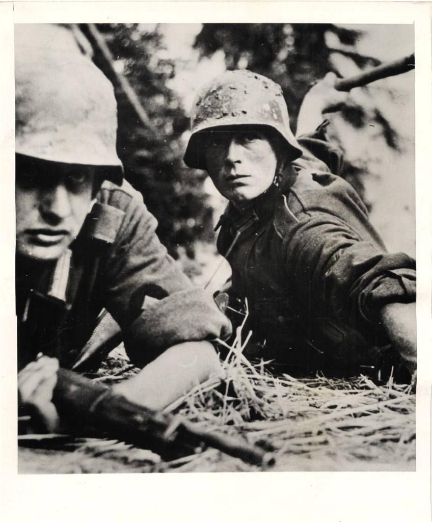 """1941- German soldier getting set to throw a hand grenade as his buddy watches with rifle ready """"somewhere"""" on the Russo-German Front."""