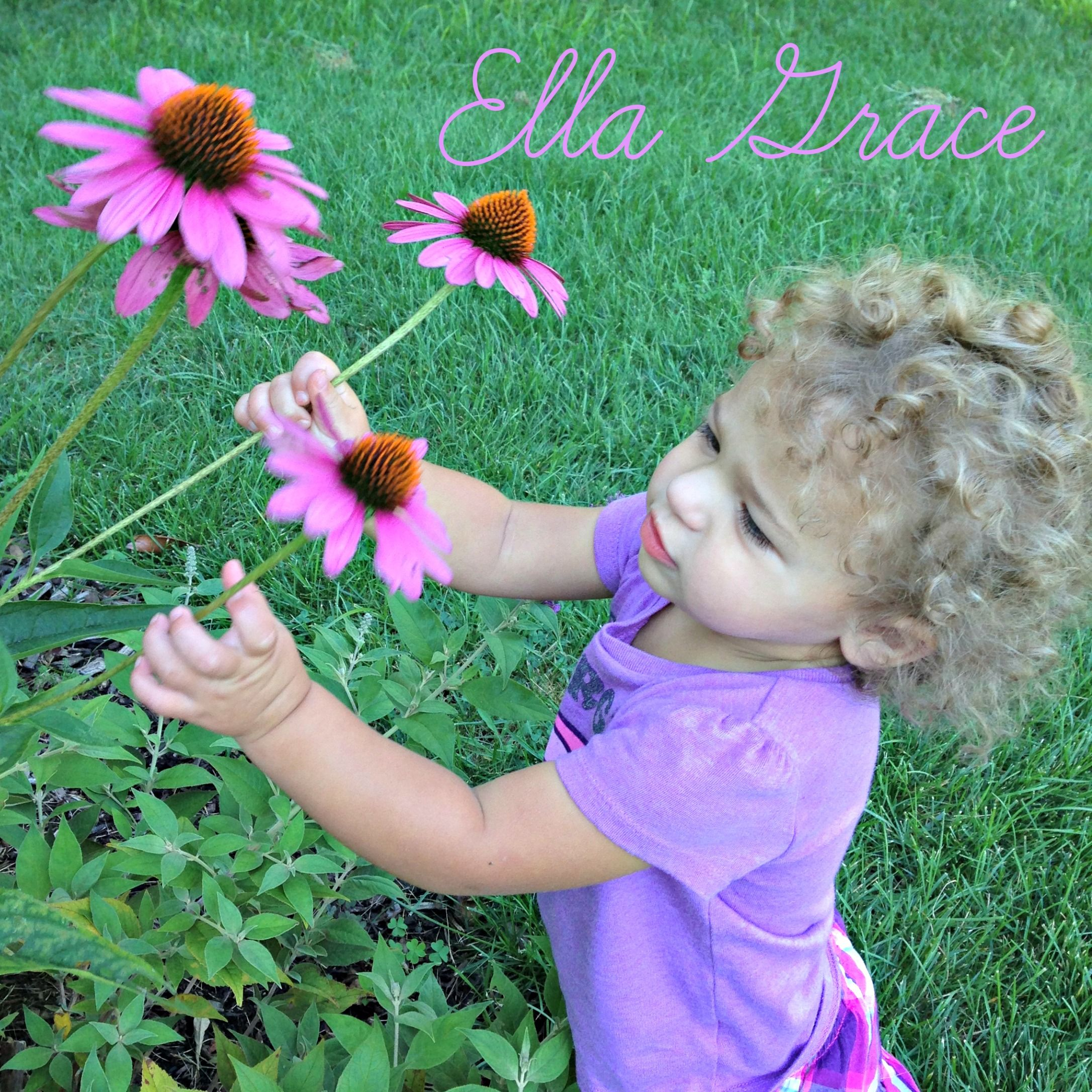 Baby smelling flowers beautiful purple curly hair