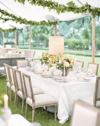 A Tented Wedding Reception: Wooden lamps with raw-burlap shades illuminate centerpieces of greige cement pots filled with dahlias, hydrangeas, and ranunculus. Upholstered seats flank rectangular tables.