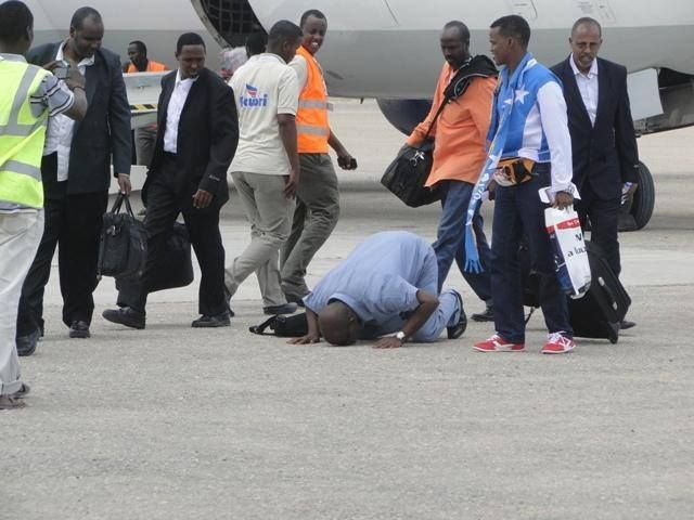 Somali diaspora returning home. A man shows his patriotism and affection by kissing the sand as the plane lands Mogadishu International airport.