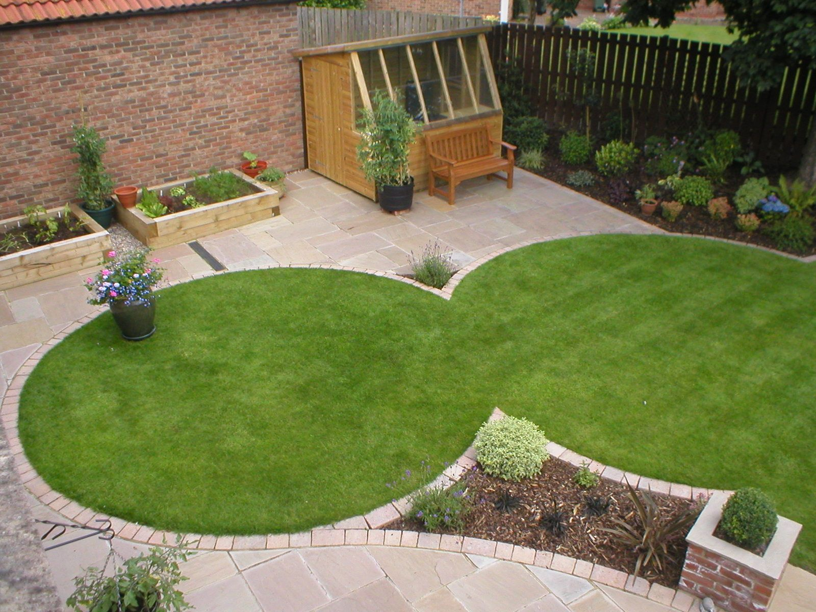 intersected circle lawns surrounded by patio with angled plantg space slanted windo wall shed in far l corner for sunl - Garden Design Circles