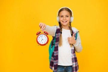 girl manage time correctly schoolgirl casual style hold retro alarm clock autumn education period child listen music earphones time management in childhood exam deadline...