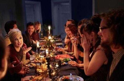 Prestretý stôl s horiacimi sviečkami a spokojnými hosťami.