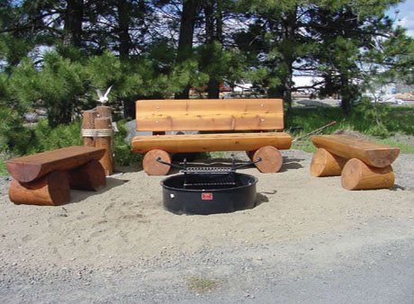 Log Bench Around A Campfire Pit In The Back Yard