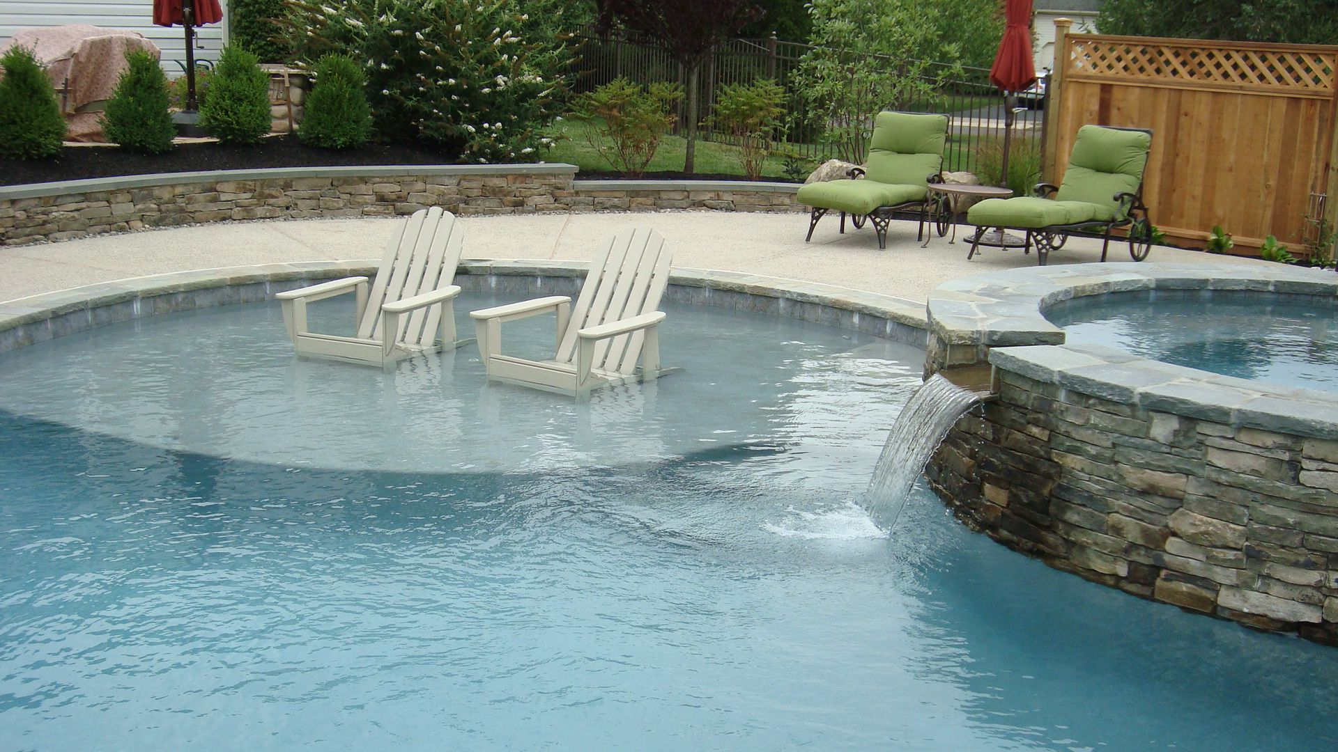 custom swimming pool with sun shelf and raised spa home