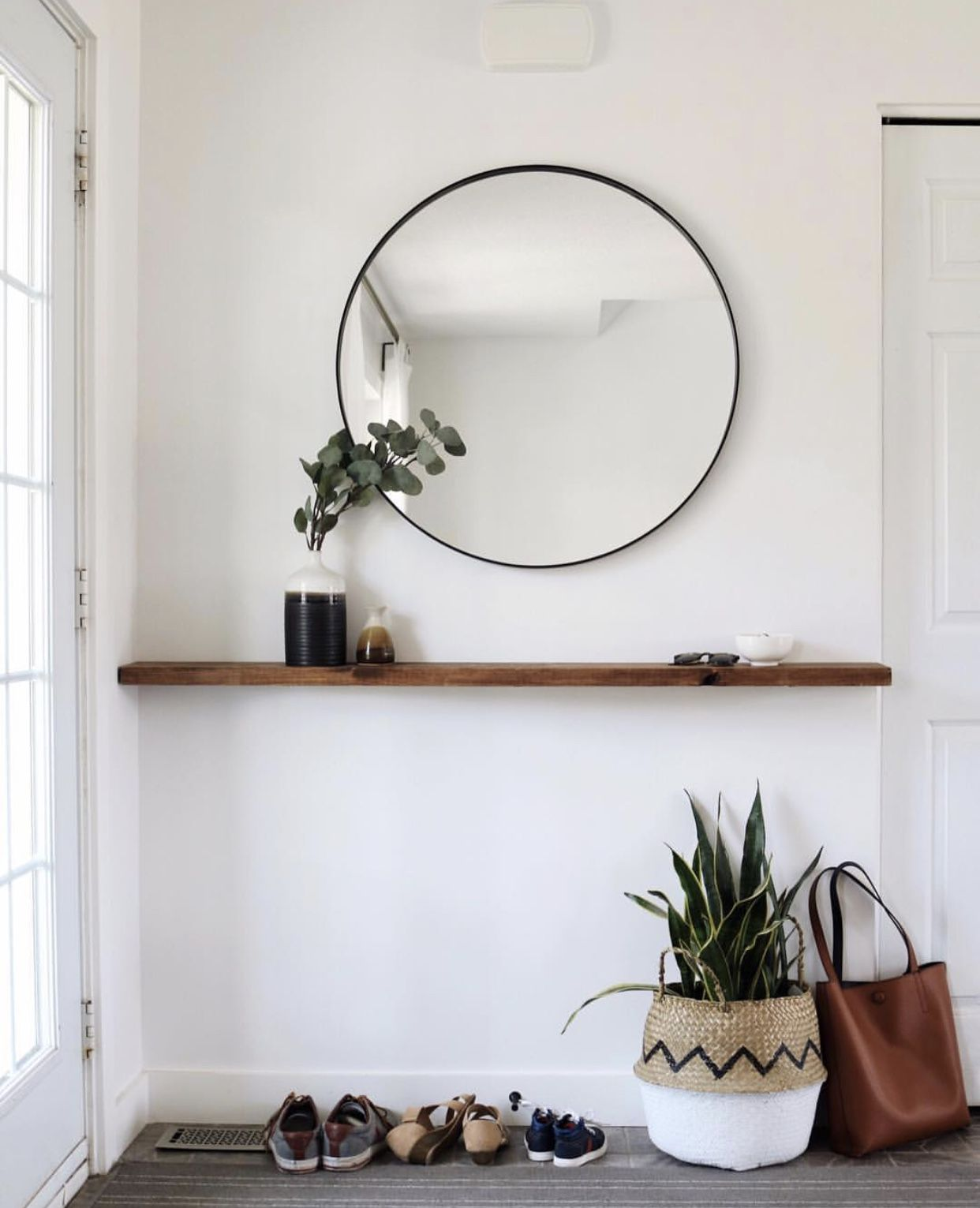 This Simple Entryway Has A Level Of Elegance With The Circular Mirror The Floating Shelf Is A Great Spot To Shelf Decor Bedroom Small Entryways Entryway Decor