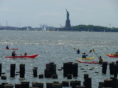 Kayaking In The New York Harbor With The Statue Of Liberty In The Background