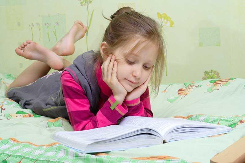school girl reading book in bed