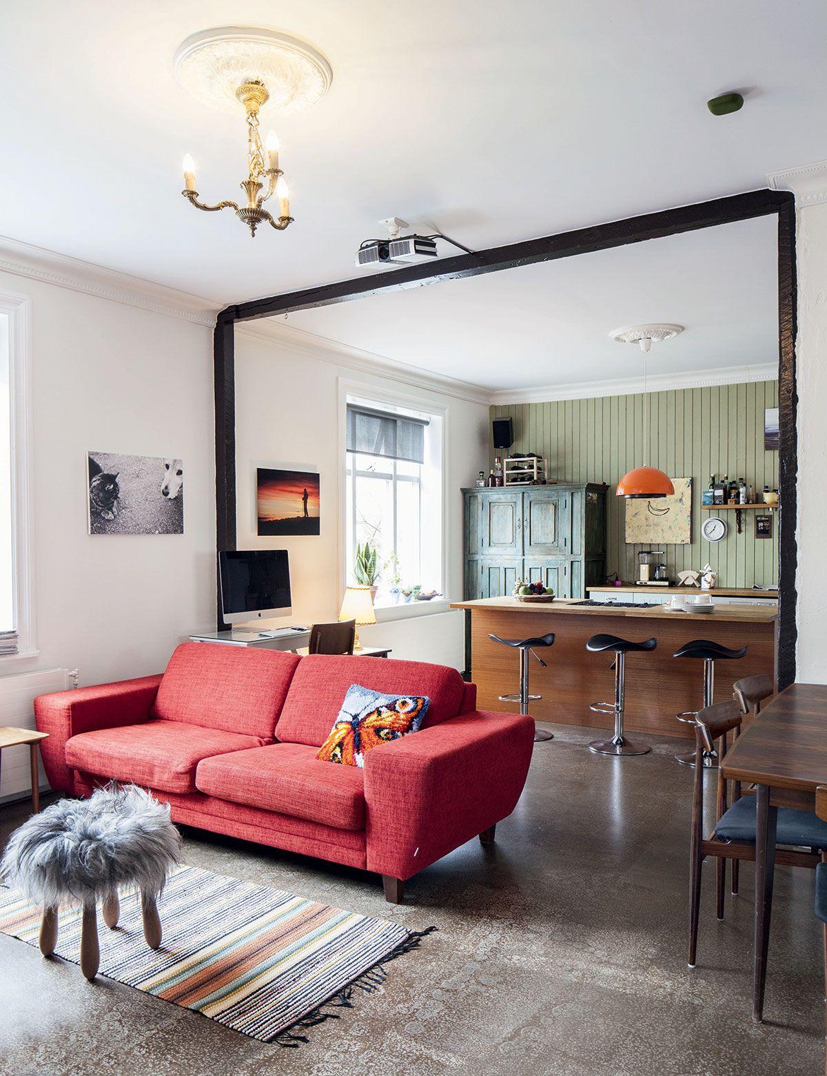 Olohuoneen keskivaiheilla olevat puiset raamit merkkaavat kohtaa, jossa on joskus ollut seinä. Punainen sohva on ostettu paikallisesta huonekaluliikkeestä. Kodissa on kauttaaltaan betonilattiat.