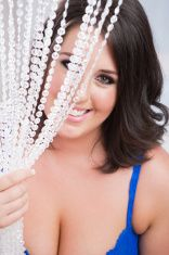 Sexy young woman in blue lingerie peeking through beaded curtain stock photo