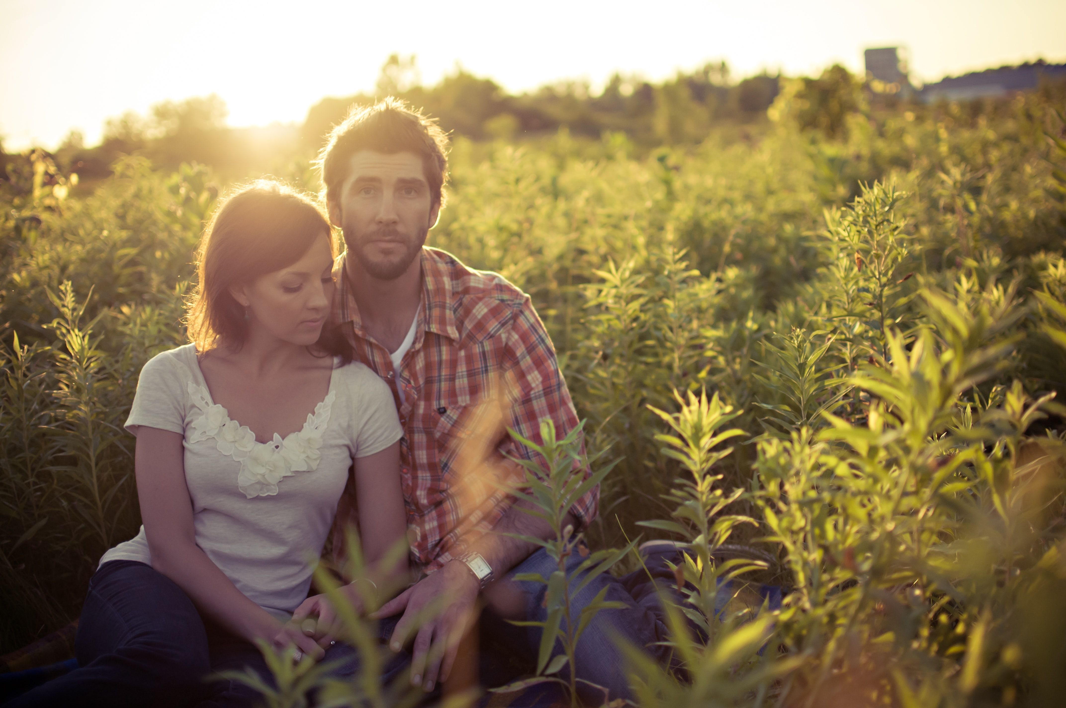 #human  #person  #plant #man #and #woman  man and woman sitting on grass field at daytime As the sun goes down…