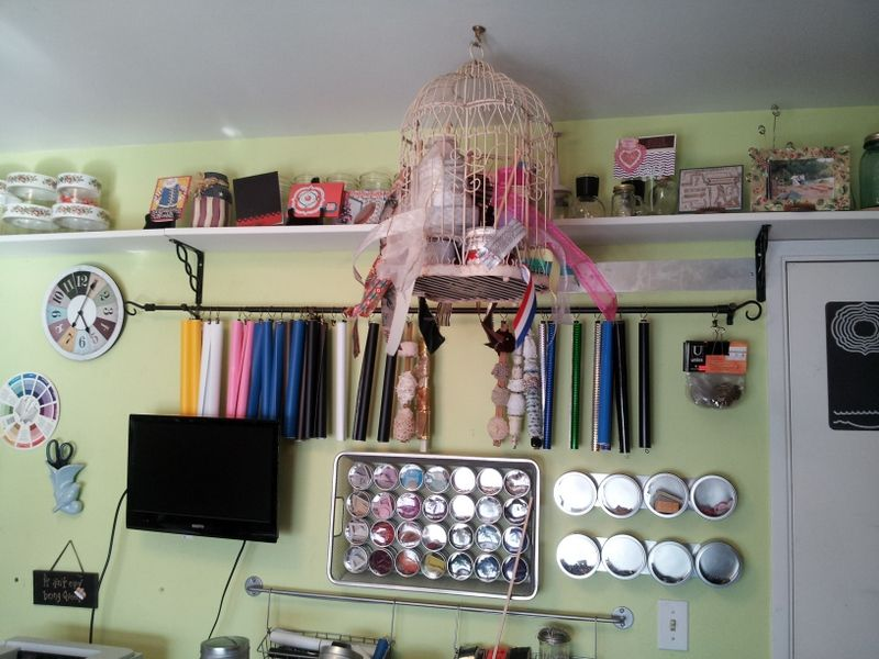 Ribbon Storage in birdcage.  Cricut vinyl on curtain rod, hanging from curtain clips, yard sale $1 per 10 clips.  Also, wooden rulers hanging on rod with lace & dingle balls.  Circles with clear fronts are misc storage in magnetic spice containers.  Thankx Pinterest!  Birdcage idea was mine!