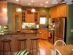 honey oak kitchen cabinets with black countertops and green walls
