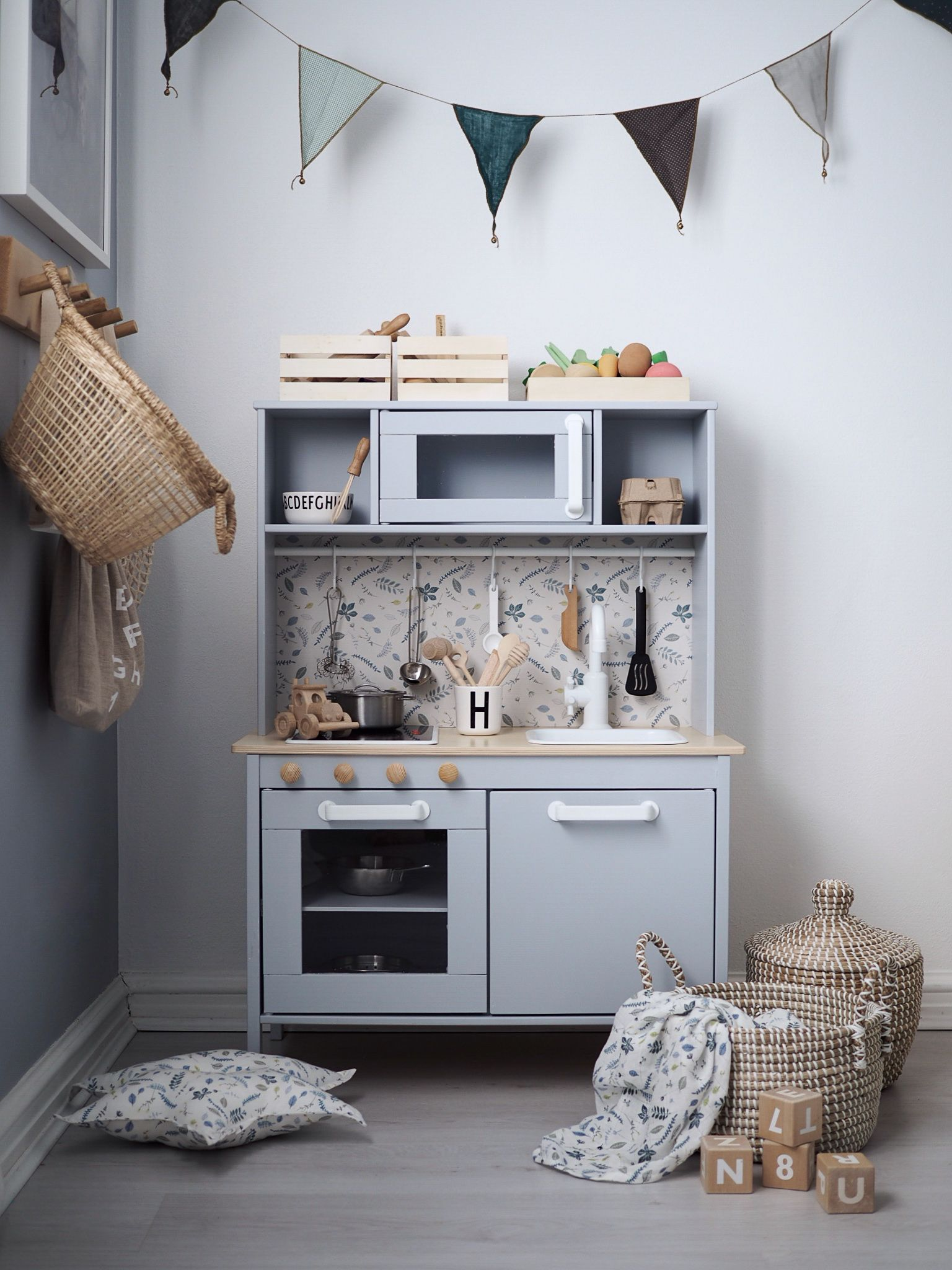 Stunning Ikea play kitchen Hack by @Ellebear. Paint is by Dulux (Miller Mood) and the splashback is Pressed Leaves blue Wallpaper by Cam Cam Copenhagen.