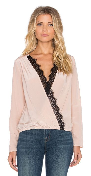Longsleeve cross over top by LIV. 100% silk. Dry clean only. Lace trim. Elasticized waist. LIV-WS36. LIV986 T1. is the LA based bra...
