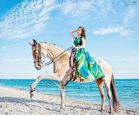 Фото Девушка в летнем цветном платье сидит верхом на ...