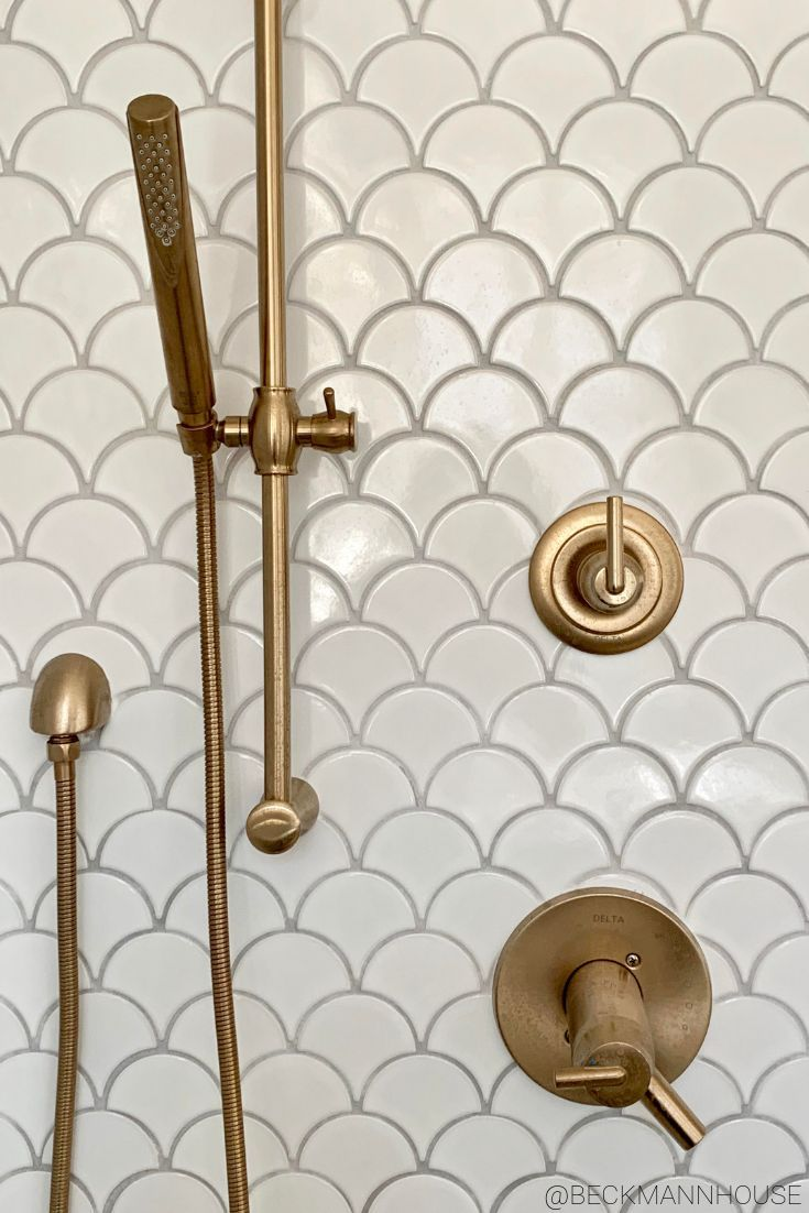 Photo of Brass accents on white scallop tiles from Beckmann House. #showerdesign #shower #ba …