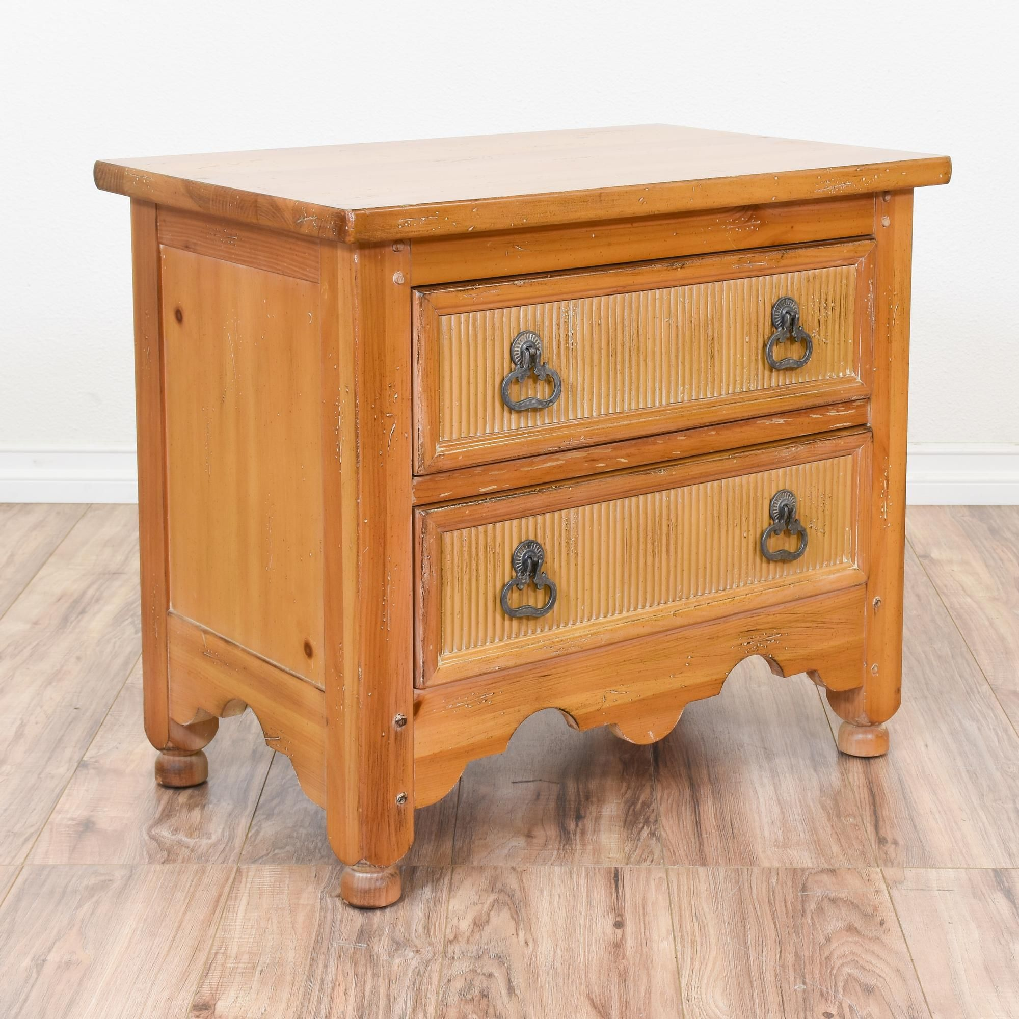 This moorish inspired nightstand is featured in a solid wood with a rustic pine finish. This end table is in great condition with 2 drawers, carved arch details and ridge panels. Unique bed side table with tons of storage! #mediterranean #dressers #nightstand #sandiegovintage #vintagefurniture