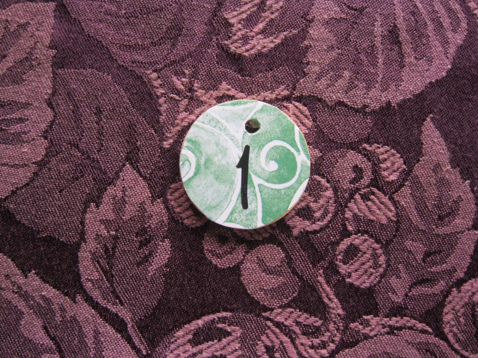 Cover a wood craft disc w/ mod podge. Cut out a circle from craft paper, apply, add a thick coat of glossy cover when it's dried. District necklaces.