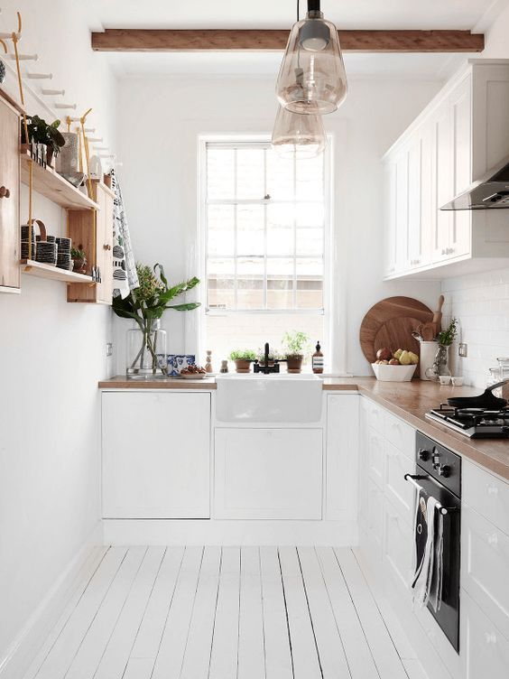 All white small kitchen, with wood bench.. a country side feeling ...