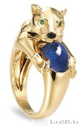 A sapphire and emerald panther ring by Cartier. The ring is shaped like a gold panther that curls around the finger, holding a cabochon sapphire. The panther has an onyx nose and emerald eyes.